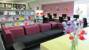 Comfortable seating area showing library journals in the background and a vase of flowers on a table in the foreground